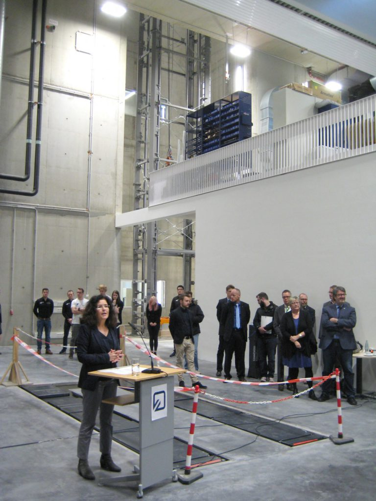 Lower Saxony science minister Gabriele Heinen-Kljajic in the institute research hall, with Ostfalia president Prof. Dr Rosemarie Karger, institute director Prof. Dr Thomas Gänsicke and the state-of-the-art drop tower in the background